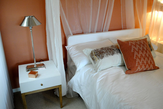Copper accents and wall paint with white bed and tulle