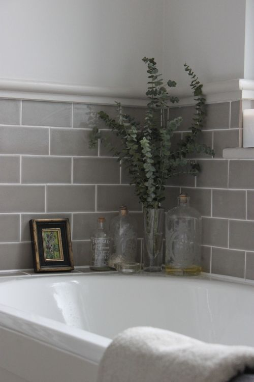grey tiles in bathroom with glass vases and bottles reflective accessories