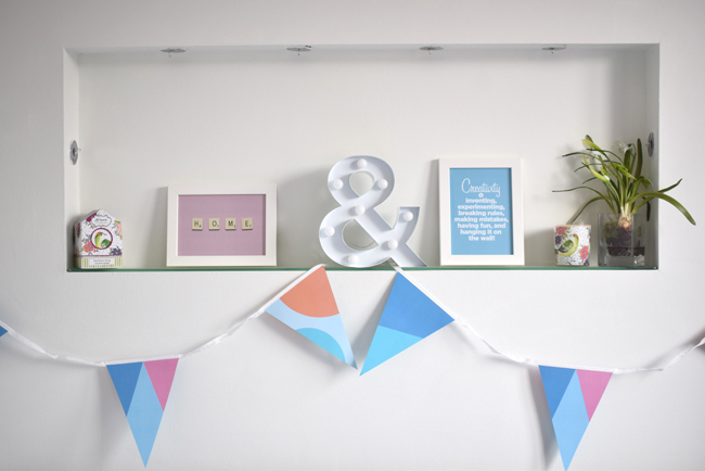 shelf styling ideas for spring with blue and pink frames