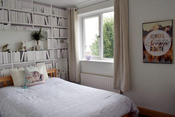 white bedroom with bookshelf wallpaper