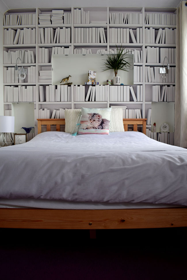 wooden bed frame in a white bedroom